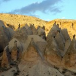 Sunset reflected on high cliffs overlooking Cappadocia with smaller formations already in shadow