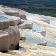 Pamukkale means cotton castle in Turkish and the name is fitting for this geological wonder where mineral rich waters tumble down the hillside leaving a gleaming white terrain that looks...